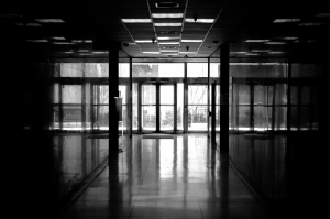 Black and white image of a laboratory hallway, glass doors in the distance