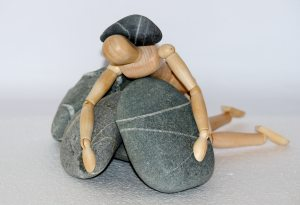 Small wooden artists' mannequin lyning prone on large grey pebbles with quartz lines